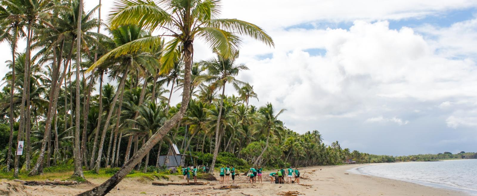 Volunteers in the South Pacific work together to clear rubbish off a beach in Fiji.